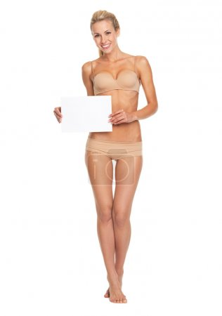 Full length portrait of happy young woman in lingerie showing blank paper sheet