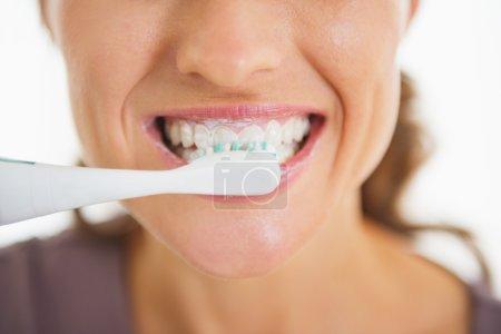 Closeup on happy woman brushing teeth