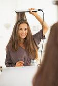 Portrait of happy woman straightening hair with straightener