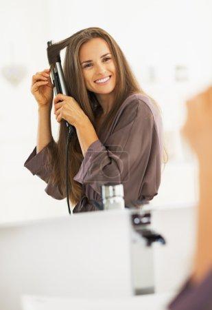 Photo pour Femme souriante cheveux frisés avec lisseur - image libre de droit