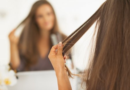 Closeup on woman checking hair after straightening