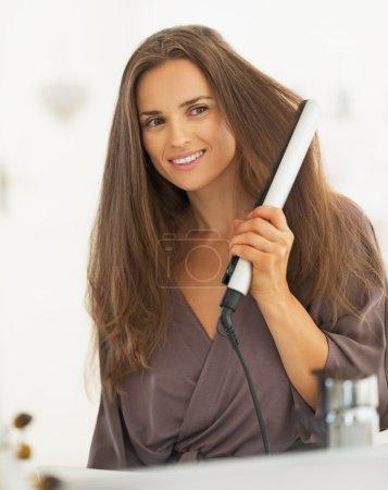 Photo pour Jeune femme bouclant les cheveux avec lisseur - image libre de droit