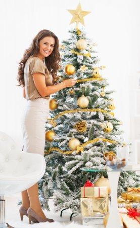 Photo pour Portrait de pleine longueur d'heureuse jeune femme décoration arbre de Noël avec la boule de Noël - image libre de droit