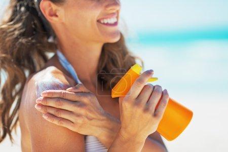 Closeup on smiling young woman applying sun block creme