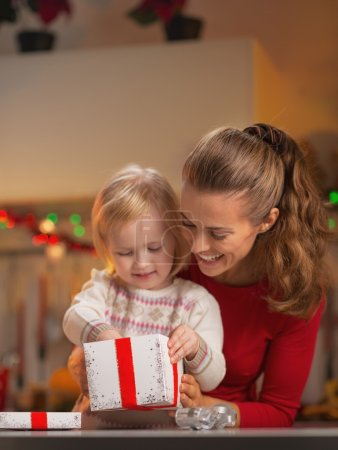 Photo for Happy mother and baby opening christmas present box - Royalty Free Image