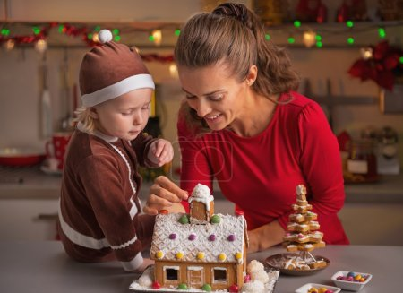 Happy mother and baby decorating christmas cookie house