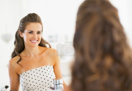 Portrait of smiling young woman looking in mirror