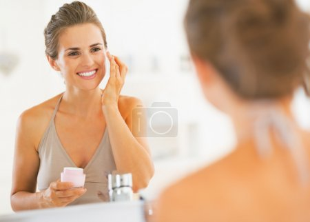 Happy young woman applying cream in bathroom