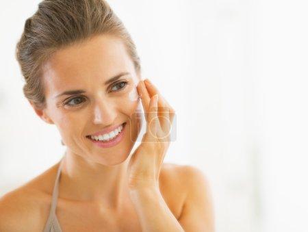 Photo pour Portrait de jeune femme heureuse appliquant de la crème dans la salle de bain - image libre de droit