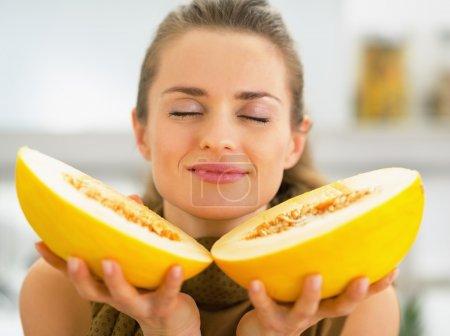 Photo pour Jeune femme appréciant le melon - image libre de droit