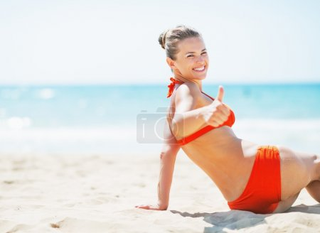 Smiling young woman sitting on beach and showing thumbs up