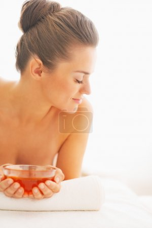 Young woman laying on massage table with honey plate