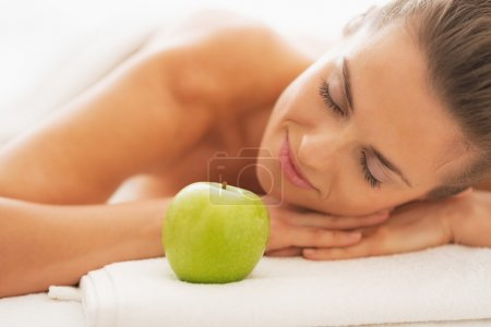 Portrait of relaxed young woman on massage table with apple