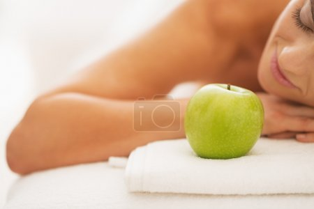 Closeup on relaxed young woman on massage table with apple