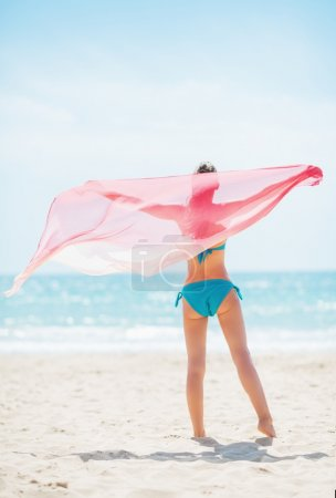 Young woman with parero rejoicing on beach.