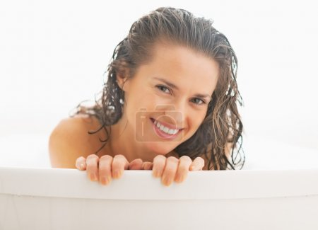 Portrait of young woman looking out from bathtub