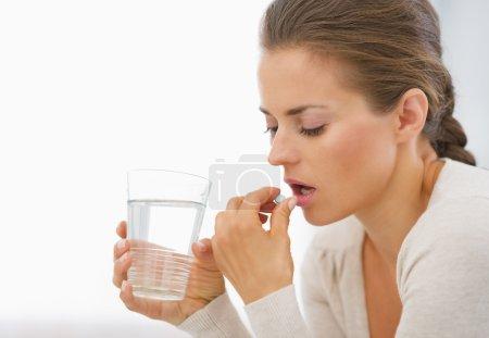 Photo pour Jeune femme manger des pilules - image libre de droit