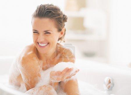 Photo pour Portrait de jeune femme heureuse jouant avec la mousse dans la baignoire - image libre de droit