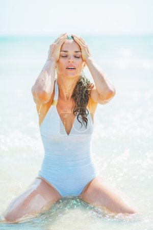 Young woman in swimsuit washing face with sea water
