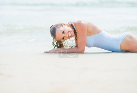 Young woman in swimsuit laying on sea shore