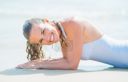 Portrait of smiling young woman in swimsuit laying on sea shore