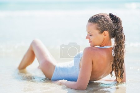 Relaxed young woman in swimsuit laying at seaside. rear view