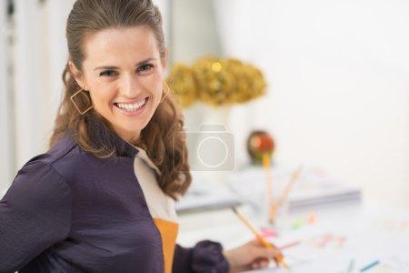 Smiling fashion designer in office
