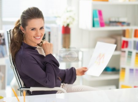 Happy fashion designer with sketch