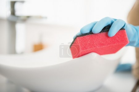 Housewife cleaning sink with sponge