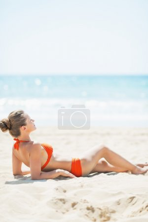 Relaxed woman laying on beach