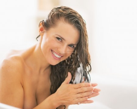 Woman applying hair conditioner