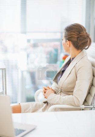 Foto de Mujer de negocios sentada en la oficina y mirando por la ventana. visión trasera - Imagen libre de derechos