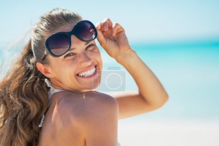 Happy young woman in sunglasses on beach