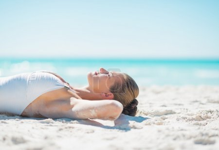 Relaxed woman tanning on beach