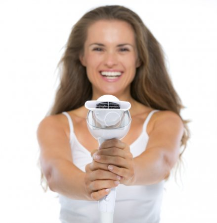 Woman pointing hairdryer in camera