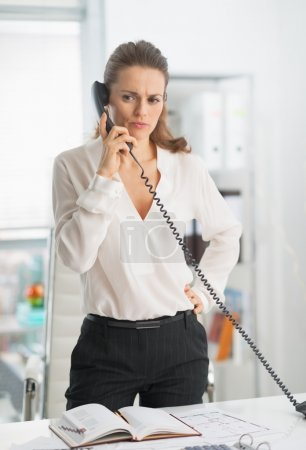 Business woman talking phone in office
