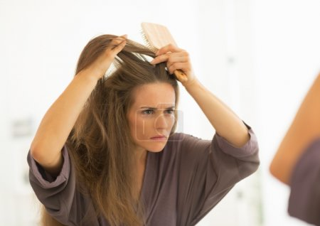Woman combing hair in bathroom