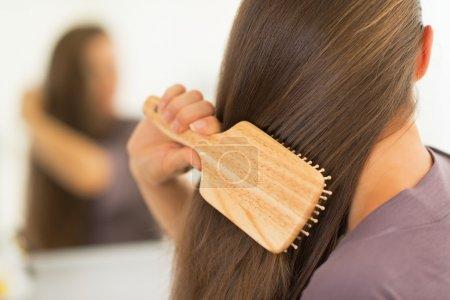 Photo pour Gros plan sur la jeune femme peigner les cheveux - image libre de droit