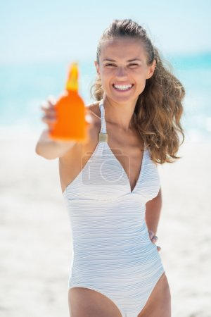 Woman showing sunscreen creme