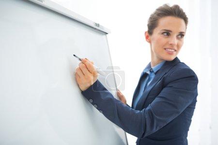 Business woman writing in flipchart