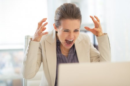 Photo for Stressed businesswoman with laptop at work - Royalty Free Image