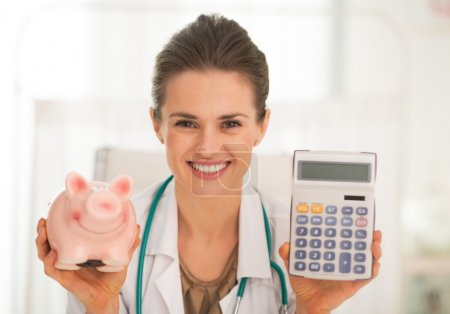 Doctor showing piggy bank and calculator