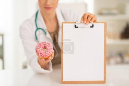Doctor woman showing blank clipboard
