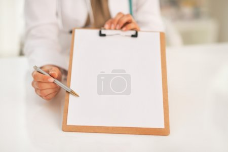 Medical doctor woman pointing in clipboard