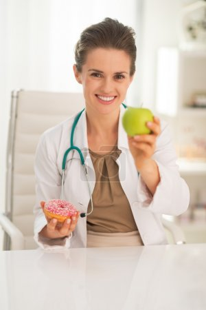 Doctor woman giving apple instead of donut