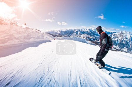 Snowboarder riding fast, motion blur, fisheye shot