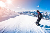 Snowboarder riding fast, motion blur, fisheye shot