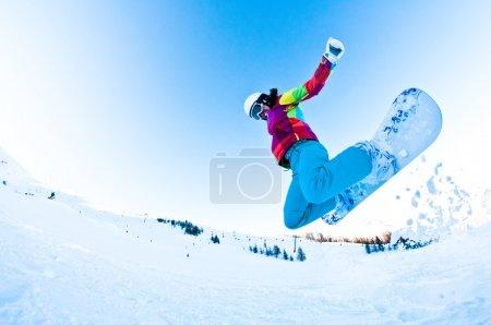 Girl snowboarder having great fun jumping