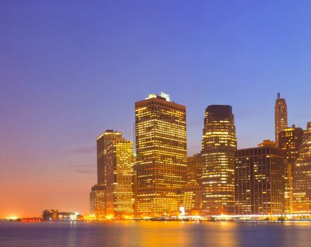 Photo for New York City USA, lights on the buildings in lower Manhattan are reflected in the water during colorful sunset - Royalty Free Image