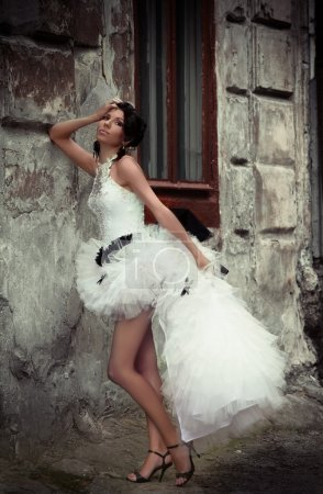 Beautiful bride leaning against the wall of an old building
